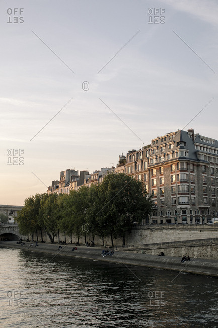 France, Paris - May 5, 2017: Buildings by Seine River against sky during sunset in city