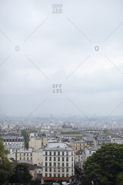France, Paris - May 6, 2017: Aerial view of cityscape against cloudy sky during foggy weather