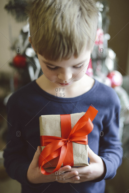 Boy holding gift while standing against Christmas Tree at home