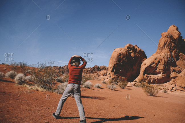 Boy standing against rock formations and sky at Valley of Fire State Park during sunny day