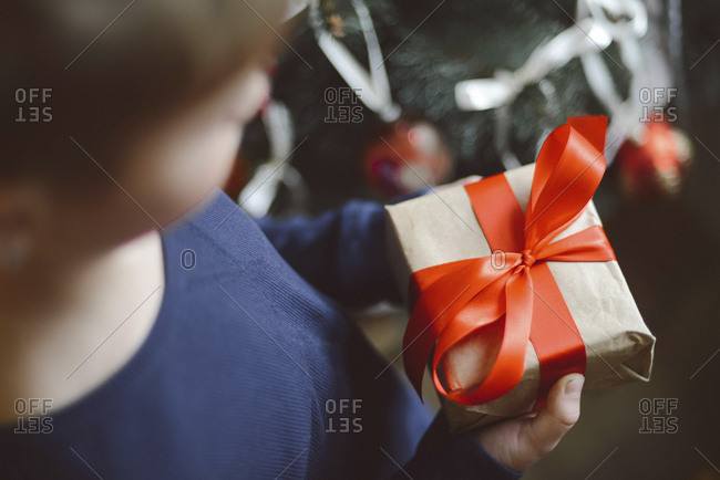 Close-up of boy holding gift by Christmas Tree at home