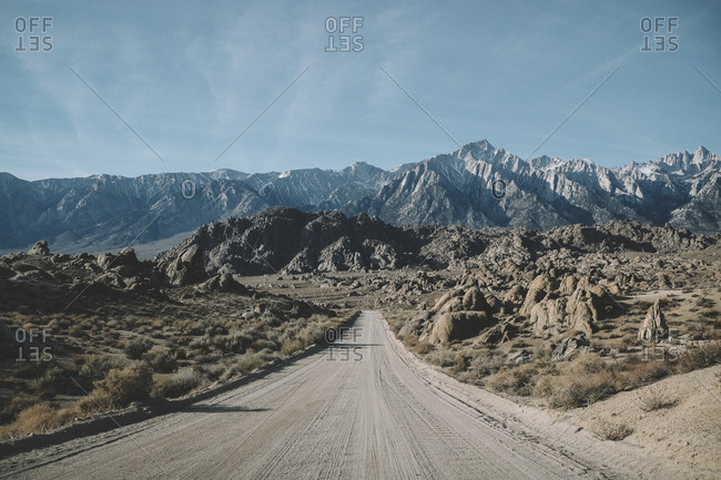 Dirt road amidst desert against mountains and sky