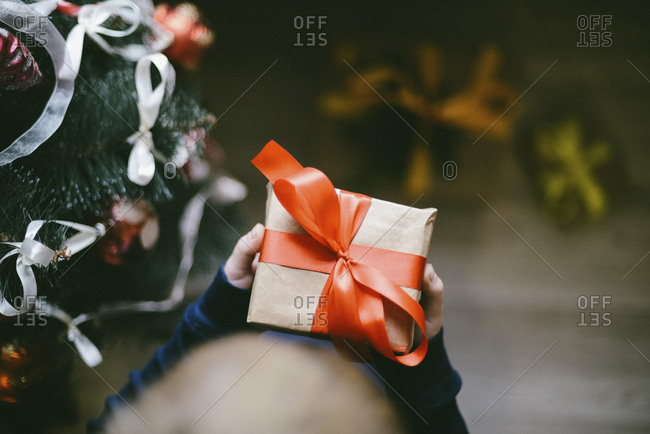 Cropped hands of boy holding gift by Christmas Tree at home