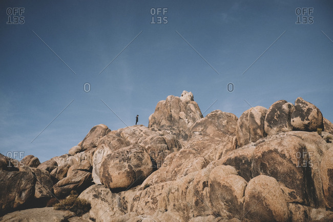 Distant view of boy on rock formations against sky at desert