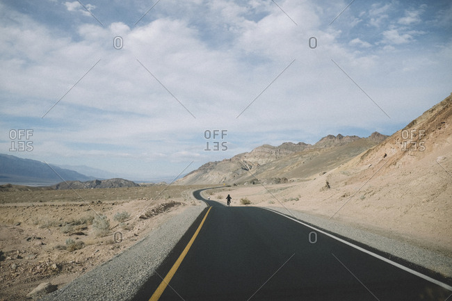 Distant view of father and son riding bicycles on desert road against cloudy sky