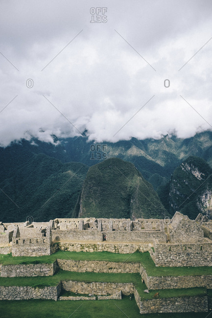 High angle view of old ruins and mountains against cloudy sky