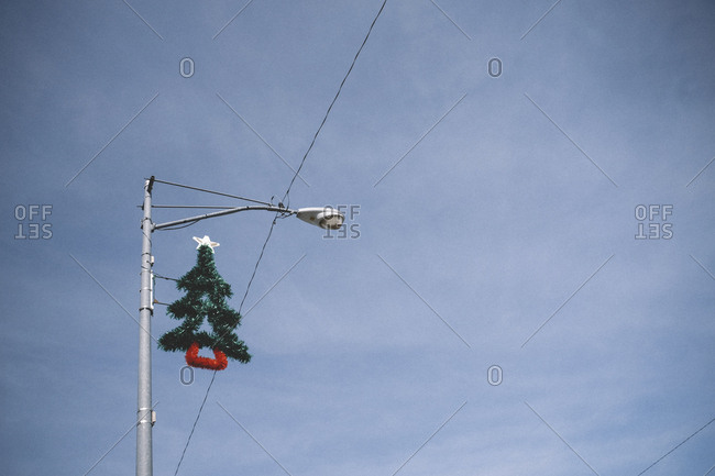 Low angle view of Christmas tree hanging on street light against sky