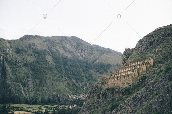 Low angle view of Ollantaytambo on mountain against sky