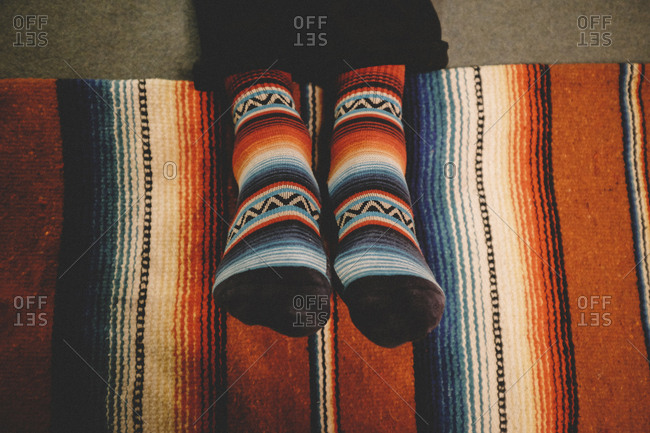 Low section of man wearing colorful socks sitting on carpet at home