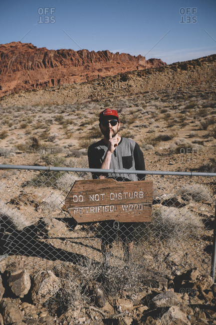 Man gesturing silence while standing by information sign on fence at Valley of Fire State Park during sunny day