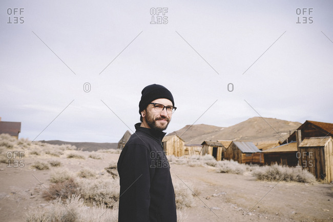 Portrait of man standing by log cabins and mountains against sky at desert