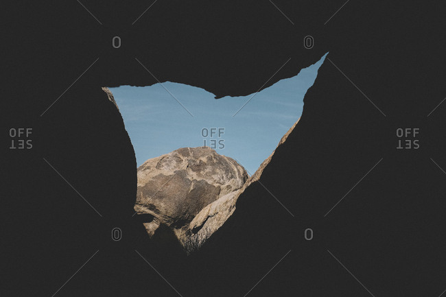 Rock formations against clear sky seen through cave