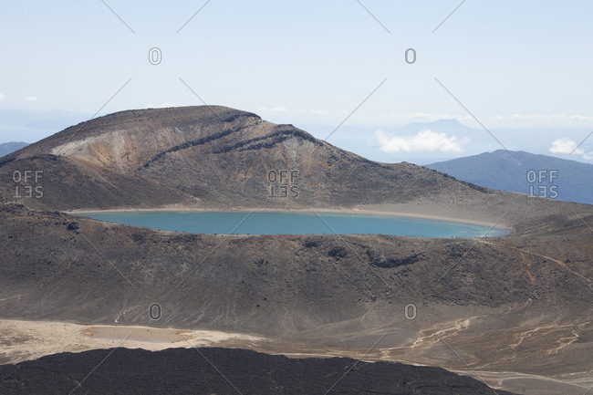 Scenic view of lake by mountains against sky during sunny day