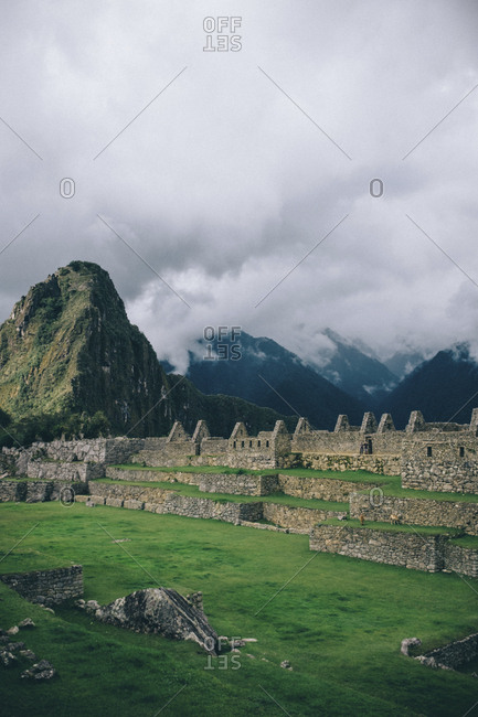 Scenic view of old ruins and mountains against cloudy sky