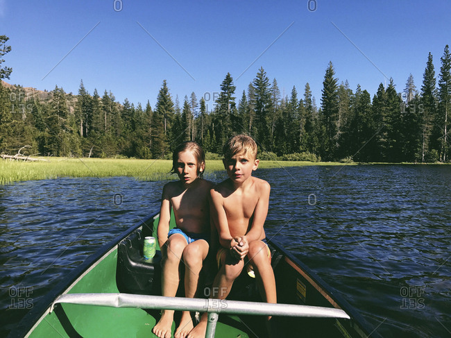 Shirtless brothers sitting in boat on Rucker Lake during sunny day at forest