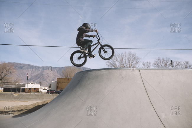 Side view of boy riding bicycle at skateboard park against sky