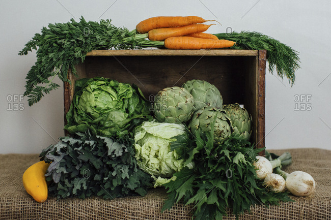 Vegetables in wooden box with burlap on table