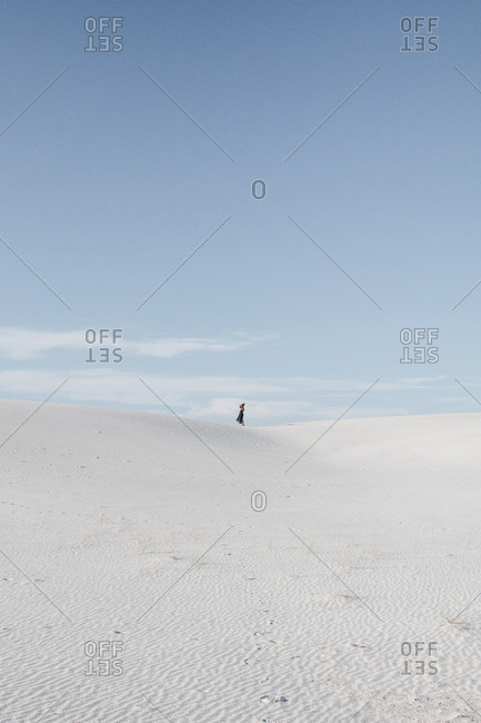 Distant view of woman standing on field against sky at White Sands National Monument