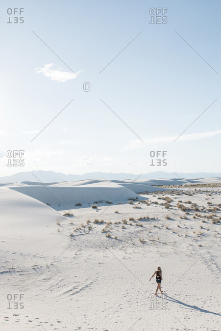 High angle view of woman walking at White Sands National Monument against sky during sunny day