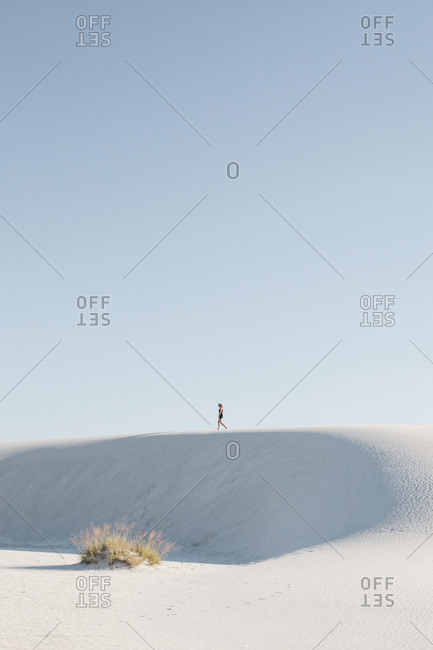 Distant view of woman walking at White Sands National Monument against clear sky