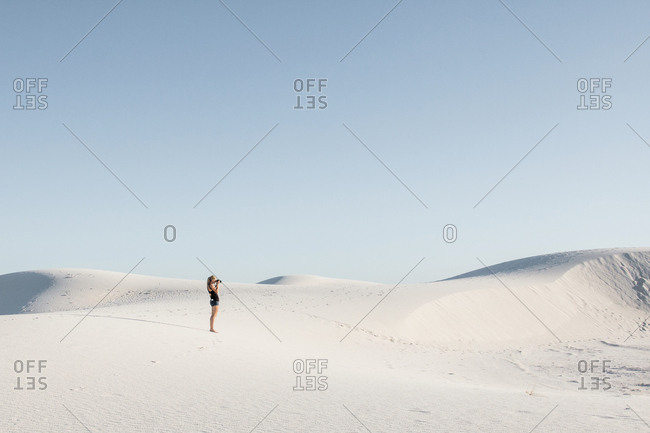 Side view of woman standing at White Sands National Monument against clear sky