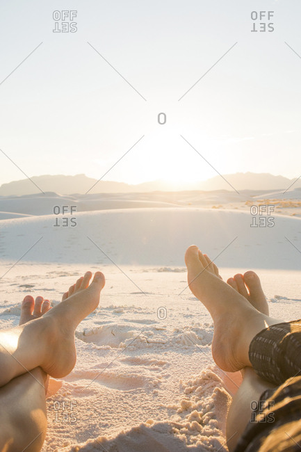 Low section of friends sitting on White Sands National Monument against clear sky during sunny day