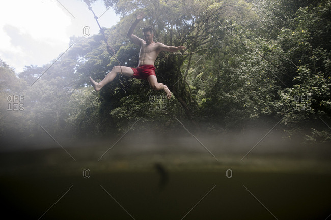 Low angle view of shirtless energetic man diving into lake at forest