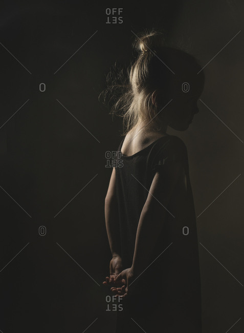 Side view of girl standing in darkroom at home