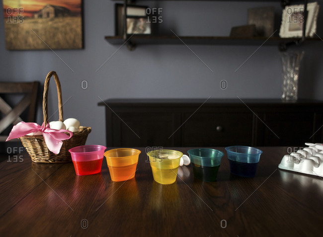 Dye in colorful bowls by eggs on wooden table at home during Easter