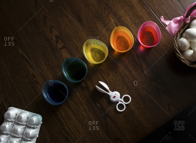 High angle view of dye in colorful bowls with eggs and spoon wooden table during Easter