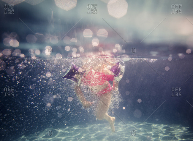 Low section of girl in swimwear swimming in pool