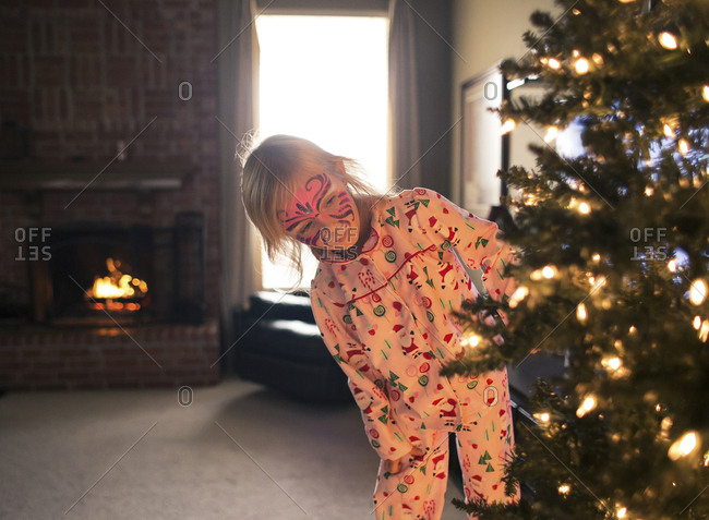 Girl with face paint looking at illuminated Christmas tree while standing in living room