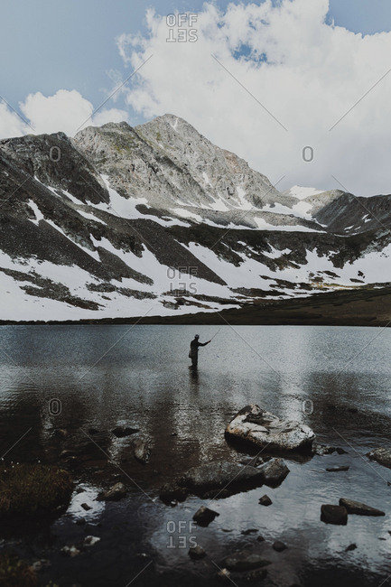 Mid distance view of man fishing while standing in lake against mountains during winter