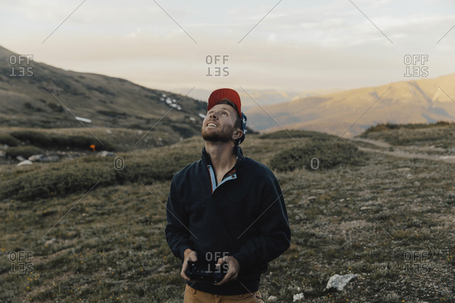 Man looking up while operating drone's remote control against mountains