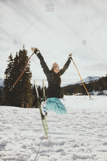 Excited young woman jumping while skiing on snowy field