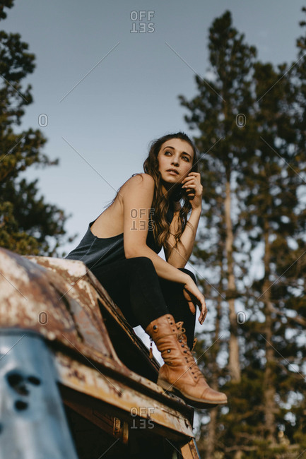 Low angle view of thoughtful young woman sitting on abandoned vehicle at forest