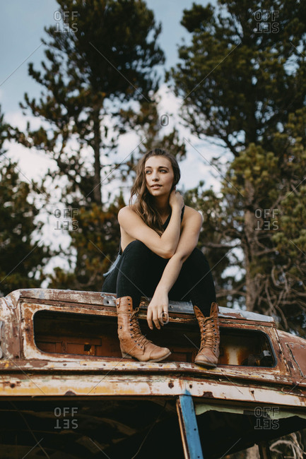 Low angle view of thoughtful young woman looking away while sitting on abandoned vehicle at forest
