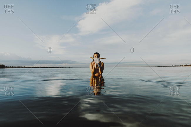 Young woman with animal skull standing in lake against sky