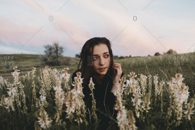 Young woman looking away while being amidst plants at park