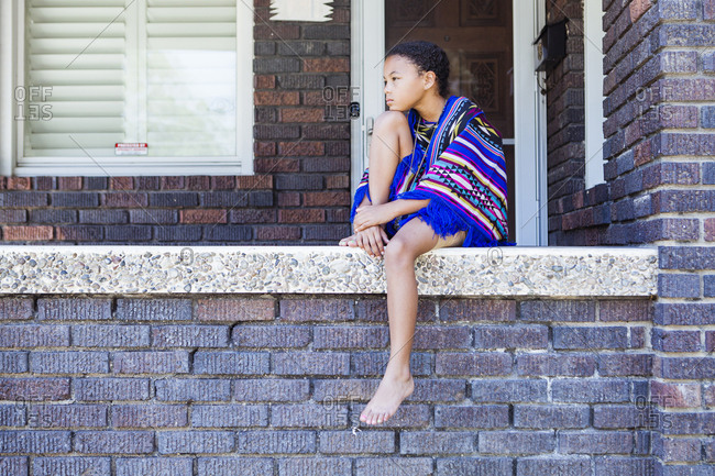 Full length of thoughtful girl with blanket looking away while sitting on retaining wall