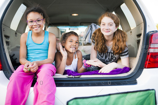 Cheerful friends playing in car trunk