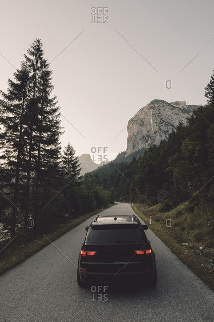 Car on road against mountain and clear sky during dusk