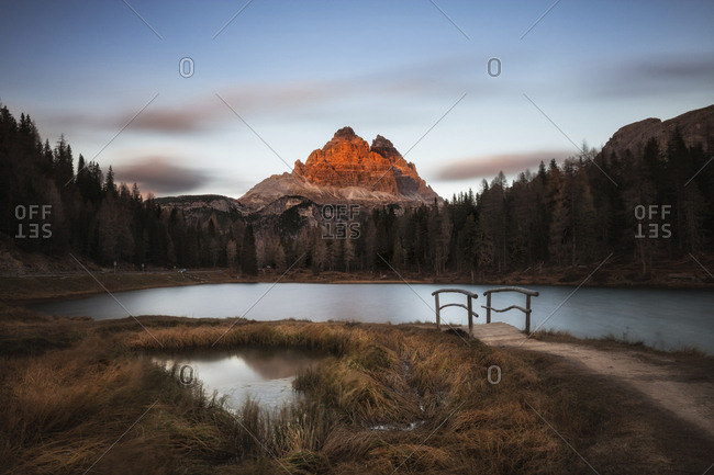 Scenic view of Lake Antorno against mountains during sunset at forest