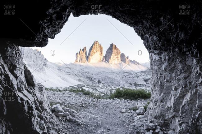 View of Tre Cime di Lavaredo seen through cave entrance