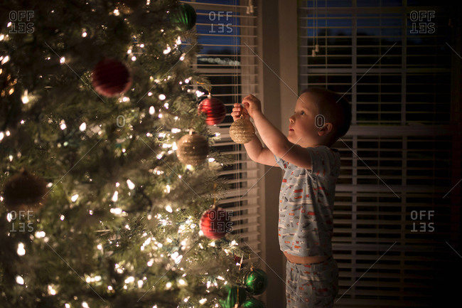 Side view of boy hanging bauble on illuminated Christmas Tree at home