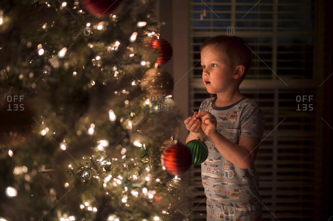 Boy holding bauble while looking at illuminated Christmas Tree