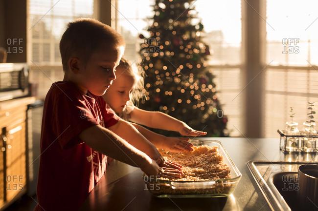 Siblings preparing food against Christmas Tree at home