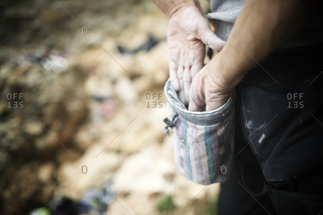 Cropped hands of hiker applying magnesium powder from bag
