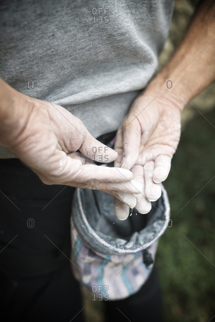 Close-up of hiker's hands applying magnesium powder from bag