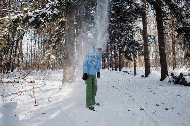 Man standing on snow covered field in forest